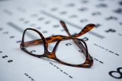 Close-up of spectacles on eye chart Royalty Free Stock Photos