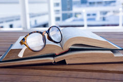 Close-up of spectacles on open book. At desk Stock Photos
