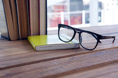 Close-up of spectacles on open book. At desk Stock Image