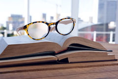 Close-up of spectacles on open book. At desk Royalty Free Stock Photo