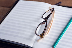 Close-up of spectacles and pencil on organizer Royalty Free Stock Photo