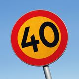 Speed limit 40. Close-up of a speed limit 40 yellow and red road sign on blue sky royalty free stock images
