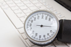 Close up of sphygmomanometer on white laptop keyboard Stock Images