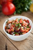 Close-up of spicy salsa dip in a bowl on wooden background royalty free stock photos