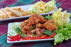 Close up of spicy sour fried chicken salad (Yum Kai Zap in Thai). As spicy chicken salad,chili,tomato,red onion,roasted rice,dried chili ,Chinese cabbage Stock Images