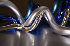 CLose up of spiral tree decorations. Close up view of shiny silver and blue spiral Christmas tree decorations on a metallic surface Royalty Free Stock Images