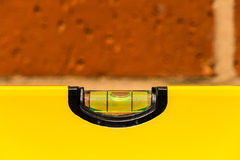 Close up of a spirit level. Showing horizontal with shallow depth of focus against a brick wall Royalty Free Stock Image