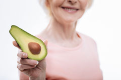 Close up of split avocado being situated in female hand Stock Photo