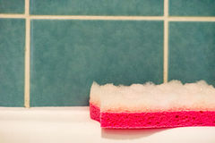 Close up of sponge on bathtub rim next to tiles Stock Photography