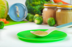 Close up of spoon with natural baby food on the table Stock Photos