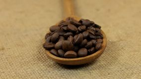 Close-up, spoon rotation with a pile of coffee beans lying on burlap. Center of rotation focus on a pile of grain stock footage