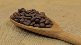 Close-up, spoon rotation with a pile of coffee beans lying on burlap. Focus on a pile of grain stock video