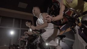 Close-up of sport group of a man and two women exercising their legs on stationary bikes. Slow motion stock video footage
