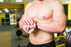 Close-up of Sportive Man After Workout Session Checks Fitness Results Smartphone. Adult Guy Wearing Sport Tracker. Wristband Arm. Training hard inside gym Stock Photography