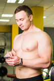 Close-up of Sportive Man After Workout Session Checks Fitness Results Smartphone. Adult Guy Wearing Sport Tracker. Wristband Arm. Training hard inside gym Royalty Free Stock Image
