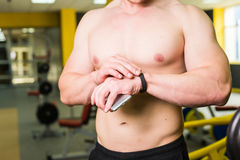 Close-up of Sportive Man After Workout Session Checks Fitness Results Smartphone. Adult Guy Wearing Sport Tracker. Wristband Arm. Training hard inside gym Stock Photos