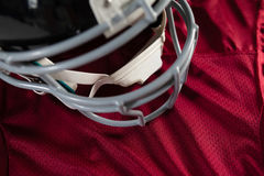 Close up of sports helmet on jersey. Close up of sports helmet on maroon jersey Royalty Free Stock Photo
