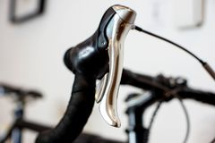 Sports racing bicycle handlebar with chrome brake lever. Close up of sports road bicycle chrome brake and shift lever. Modern athletic road bicycle with a black stock images