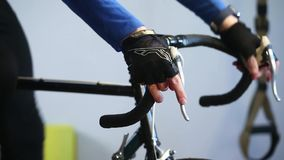 Close-up of sportsman hands working out on bicycle indoors in the gym. Smartwatch measure pulse stock video footage