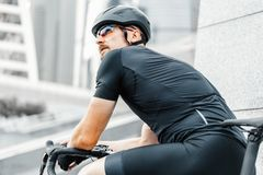 Close up of sportsman relaxing after riding bike next to modern skyscrapers. royalty free stock image