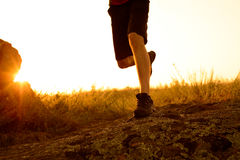 Close-up of Sportsman's Legs Running on the Rocky Mountain Trail at Sunset. Active Lifestyle Stock Image