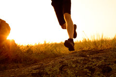 Close-up of Sportsman's Legs Running on the Rocky Mountain Trail at Sunset. Active Lifestyle Royalty Free Stock Photos