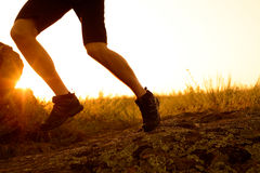 Close-up of Sportsman's Legs Running on the Rocky Mountain Trail at Sunset. Active Lifestyle Royalty Free Stock Image