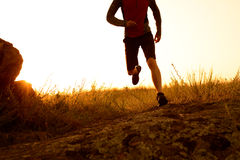 Close-up of Sportsman's Legs Running on the Rocky Mountain Trail at Sunset. Active Lifestyle Stock Photography