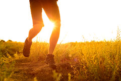 Close-up of Sportsman's Legs Running on the Rocky Mountain Trail at Sunset. Active Lifestyle Stock Photos