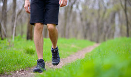 Close-up of Sportsman's Legs Walking on the Trail in the Wood. Active Lifestyle Royalty Free Stock Images