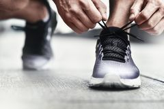 Close-up of sportsman tying sneakers. Unrecognizable man stopping lacing shoe outdoors. Athletic shoes concept. Color Version. Cropped image of hands tying royalty free stock photography