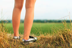 Close up of a sportwomans feet running in autumn grass royalty free stock image