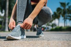 Young woman legs tying laces on sneakers. Close up of sporty girl feet squatting on the alley. She is tying shoelaces after summer sport activity royalty free stock image