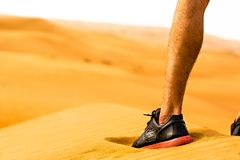 Close-up of sporty man leg/shoe standing alone in the desert. Fitness concept. stock photo
