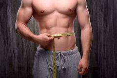 Close up of sporty man measuring his waist Stock Photo