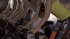 Close-up of sporty man and two young women exercising their legs on stationary bikes