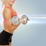 Close up of sporty woman with heavy steel dumbbell Royalty Free Stock Images