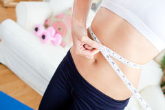 Close up of a sporty woman measuring her waist Royalty Free Stock Photos