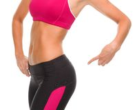 Close up of sporty woman pointing at her buttocks. Fitness and diet concept - close up of sporty woman pointing at her buttocks Stock Photography