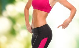 Close up of sporty woman pointing at her buttocks. Fitness and diet concept - close up of sporty woman pointing at her buttocks Royalty Free Stock Images