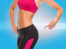 Close up of sporty woman pointing at her buttocks. Fitness and diet concept - close up of sporty woman pointing at her buttocks Royalty Free Stock Photo