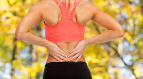 Close up of sporty woman touching her back Stock Photo