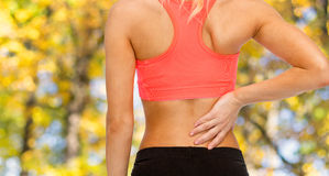 Close up of sporty woman touching her back Royalty Free Stock Photography