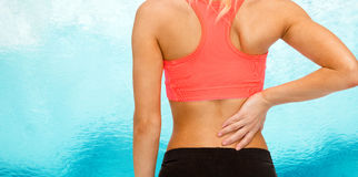Close up of sporty woman touching her back Royalty Free Stock Image