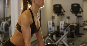 Close-up of a sporty woman training deadlift with heavy weights in fitness gym. Close-up of a young woman training deadlift strength with heavy weights. Deadlift stock video footage