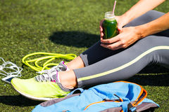 Close Up Sporty young woman holding green juice sitting on grass Stock Photos