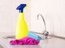 Kitchen cleaning concept. Close up of spray bottle, sponge and cleaning cloth on kitchen countertop with faucet in background. Housekeeping concept stock photos
