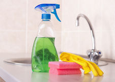 Kitchen cleaning concept. Close up of spray bottle, sponge and rubber gloes on kitchen countertop with faucet in background. House cleaning concept stock images