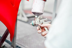 Close up of spray gun painting a car Royalty Free Stock Photo