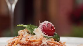 Close-up sprinkle grated tasty cheese parmesan to fresh appetizing pasta dish on plate at restaurant